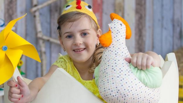 Mädchen in Hühnerkostüm schlüpft aus Ei.