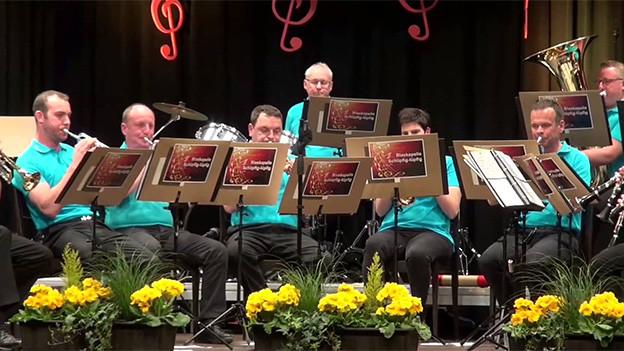 Blasmusikanten in türkisfarbenen Polo-Shirts und schwarzen Hosen während eines Konzerts sitzend auf einer Bühne.