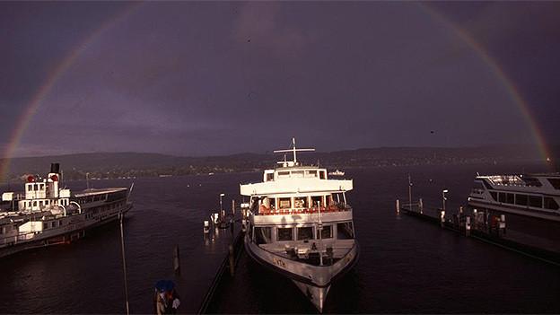 Ein Regenbogen spannt sich nach einem Gewitter über den Zürichsee, auf dem drei Kursschiffe vor Anker liegen.