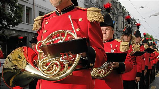 Marsch mit Blasmusikanten in roten Uniformen.