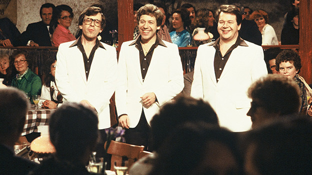 Die drei Sänger tragen schwarze Hemden und weisse Westen und singen vor Publikum.