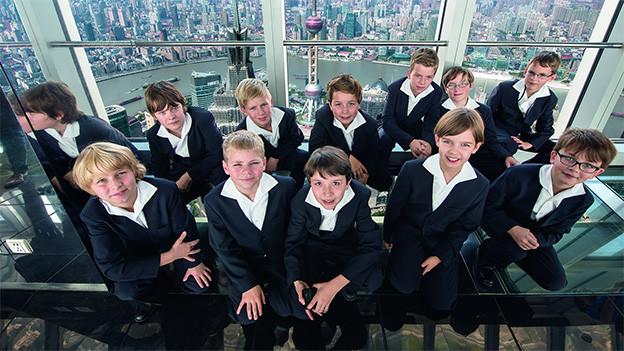 Die jungen Sänger sitzen in einem hohen Aussichtsturm mit Glasfenstern auf einer Plattform.