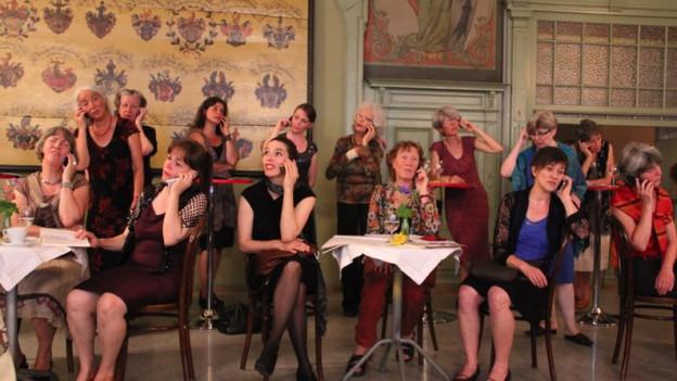 Chorsängerinnen sitzen mit Abendkleidern in einem noblen Café. Alle telefonieren mit einem Handy.