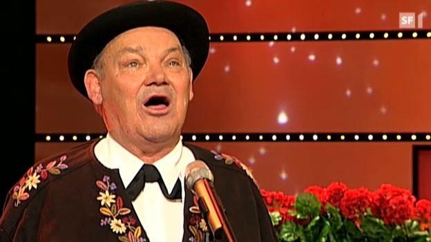 Jodler mit schwarzem Hut und braunem Sennenhemd bei einem Fernsehauftritt.