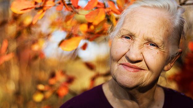 Eine ältere Frau, die vor einem Laubbaum steht und glücklich lächelt.