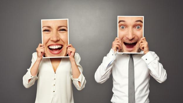 Mann und Frau halten sich ein Foto vors Gesicht mit jeweils einem grinsenden Gesicht.