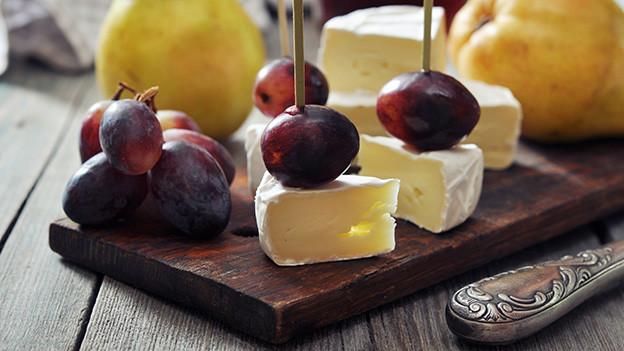Käseplatte mit geschnittenem Weichkäse, Trauben und Birnen.