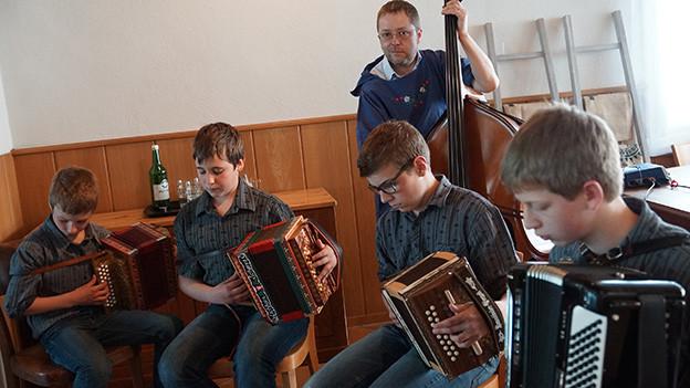 Vier junge Schwyzerörgeler werden von einem Mann am Kontrabass begleitet.