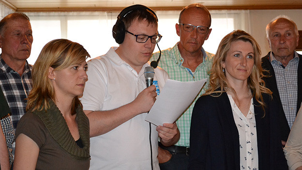 Der Moderator mit Mikrofon steht in einer Gruppe von Menschen.