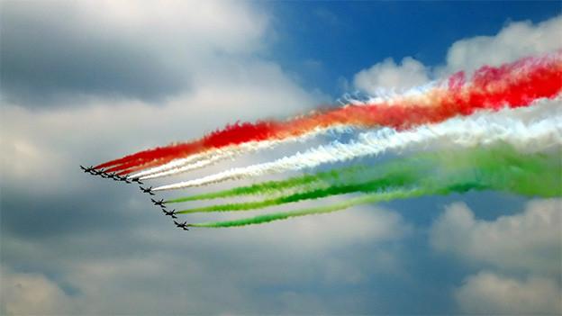 Eine Flugstaffel, die am Himmel Streifen in den Farben Rot, Weiss und Grün hinterlässt.
