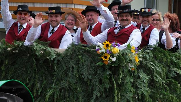Ein Gruppe von Jodlern auf einem Umzugswagen.