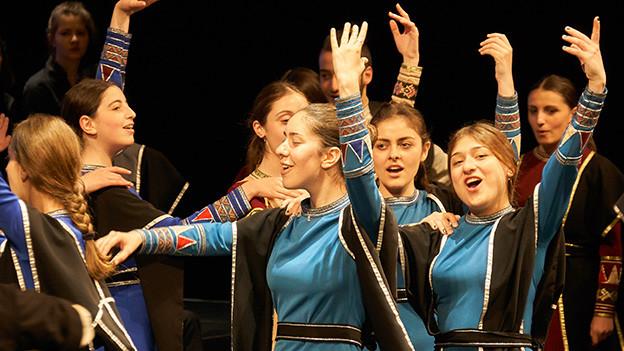 Tanzende Sängerinnen in bunten Kostümen.