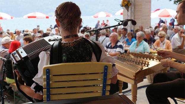 Eine Akkordeonistin auf einer Bühne mit Blick auf viel Publikum und einen See.