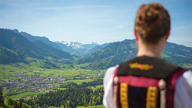 Eine Trachtenfrau blickt über die Weite einer Landschaft.
