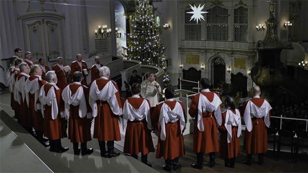 Ein Chor mit weiss-rot gekleideten Männer in einer Kirche.