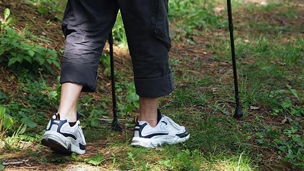 Beine und Füsse eines Wanderers mit Wanderstöcken.