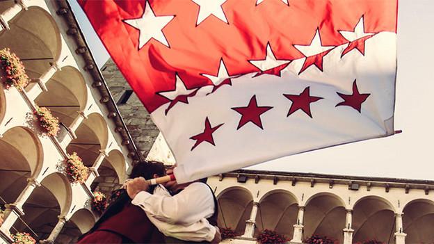 Ein Trachtenpaar tanzt, der Mann schwingt dazu eine Walliserflagge.