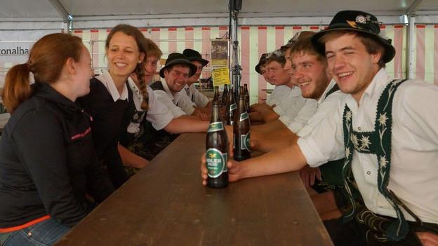Eine Gruppe junger Menschen sitzt auf Festbänken an einem langen Tisch.