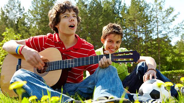Zwei Buben sitzen auf einer Wiese, der eine spielt Gitarre und singt.