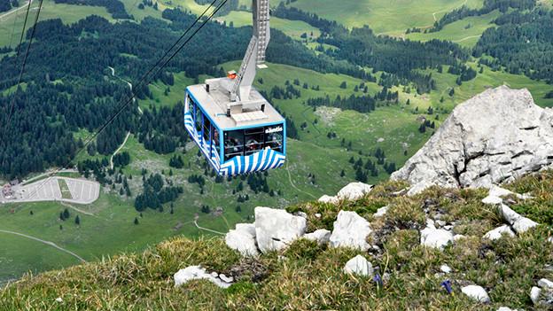Eine blau-weiss gestreifte Gondel in einer Berglandschaft.