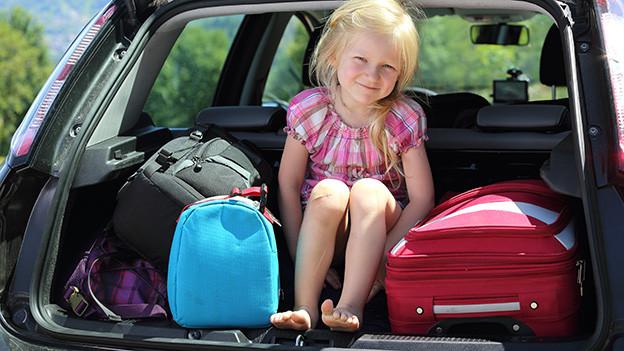 Ein blondes Mädchen sitzt in einem Kofferraum auf einem Berg von Koffern.