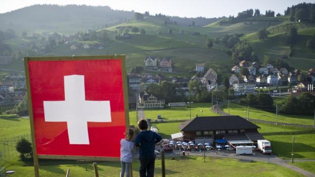 Ausblick über Appenzellerland. Im Vordergrund ein Kinderpaar neben Schweizerflagge.