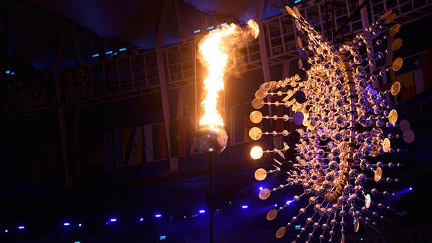 Das Olympiafeuer vor einer goldenen Installation.