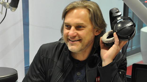 Der Moderator sitzt hinter dem Mikrofon und hält Kopfhörer in der Hand.