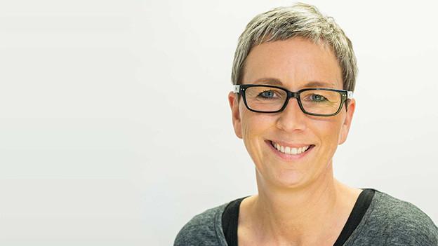 Porträt einer Frau mit kurzen blonden Haare und Brille.