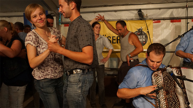 Mehrere Tanzpaare auf einer Holzbühne in einem Festzelt.