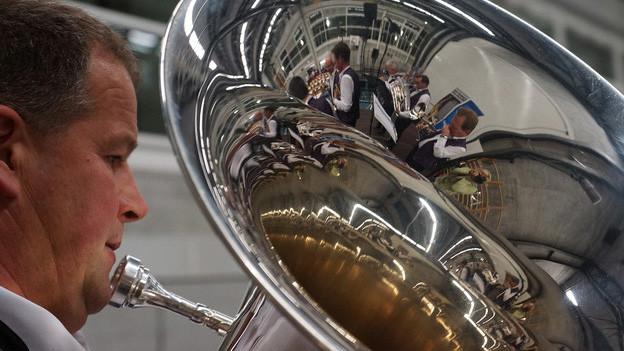 Blasmusikanten vor Notenständern. Auf der Bühne steht ausserdem ein grosser Pokal.