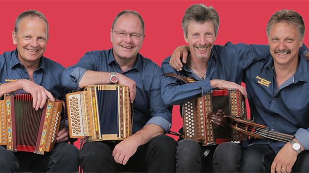 Vier Musikanten in blauen Hemden vor einem roten Hintergrund.