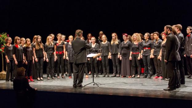 Schweizer Jugendchor mit etwa 30 Mitgliedern auf Bühne.