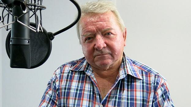 Ein älterer Mann mit kariertem Hemd sitzt vor einem Mikrofon.