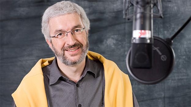 Ein Mann mit grauen Haaren und einem gelben Pullover über den Schultern sitzt vor einem Mikrofon.