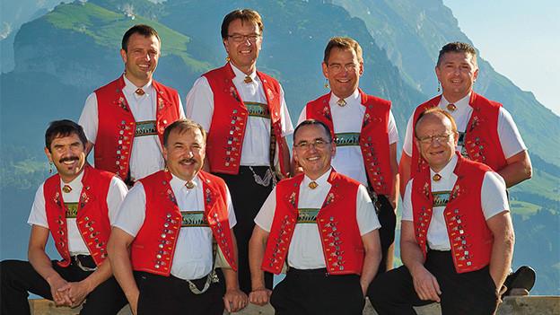 Acht Männer in Appenzeller Tracht vor einer Bergkulisse.