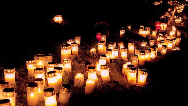 Viele weisse Grabkerzen in einer dunklen Nacht.