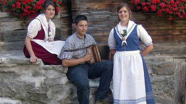 Zwei junge Jodlerinnen und ein Schwyzerörgeler vor einem Walliser Chalet.