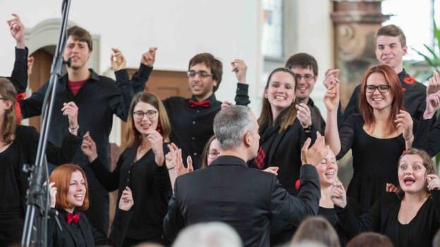 Dirigent mit Schweizer Jugendchor während Konzert.