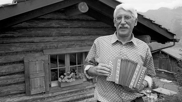 Schwarz-Weiss-Fotografie mit einem Schwyzerörgeler, der vor einer kleinen Alphütte steht.