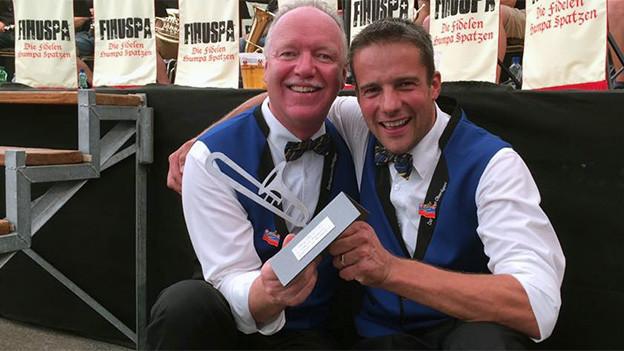Zwei Männer halten kniend eine Pokal in Form einer Musiknote.