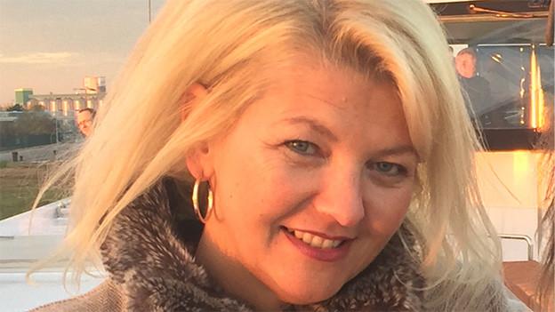 Porträt einer blondhaarigen Frau.
