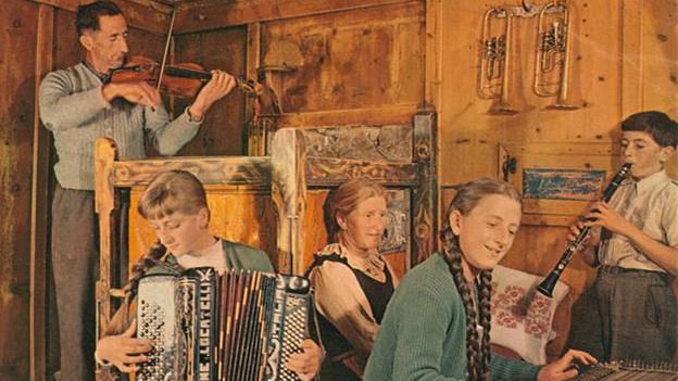 Alte Fotografie mit einer Familienkapelle, die im Wohnzimmer musiziert.