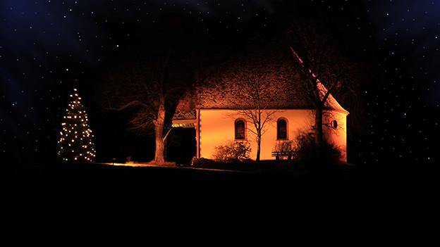 Ein Tannenbaum mit Lichtern vor einer sanft beleuchteten Kapelle.