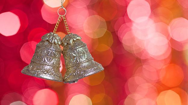 Zwei kleine silberne Glocken vor einem roten Hintergrund.