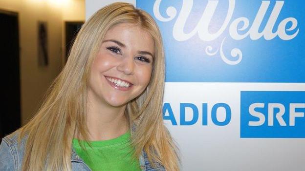 Die blondhaarige Schlagersängerin steht strahlend vor dem Logo von SRF Musikwelle.