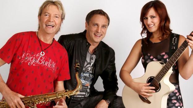 Porträtfoto des Trios, bestehend aus zwei Männern und einer Frau.