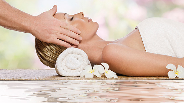 Eine Frau liegt entspannt am Rande eines Wasserbeckens und geniesst eine Kopfmassage.