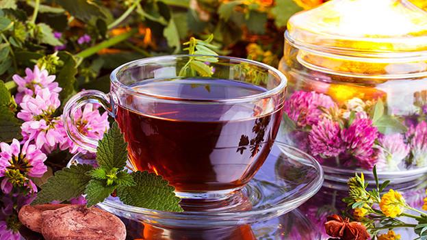 Stillleben mit einer Tasse Tee und Blumen auf einem Tisch.