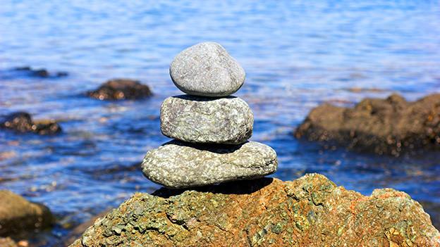 Drei aufeinander getürmte Steine am Flussufer.